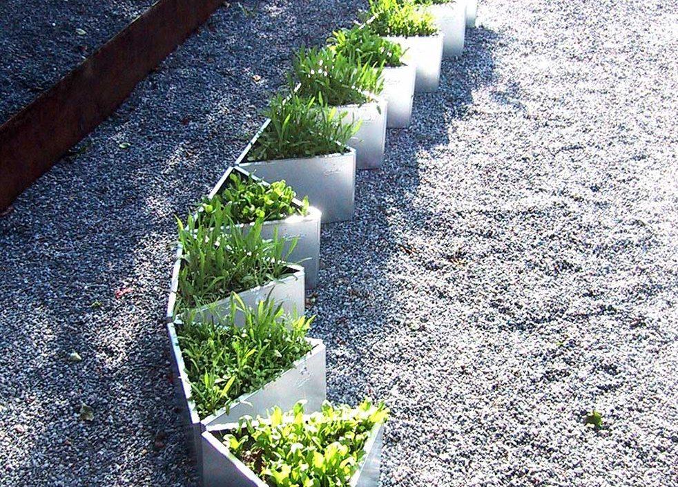 Liten trekantig odlingslådor arrangerade i en rad